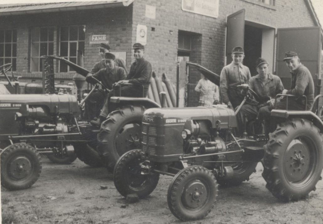 1956: Mitarbeiter auf neu angelieferten Traktoren